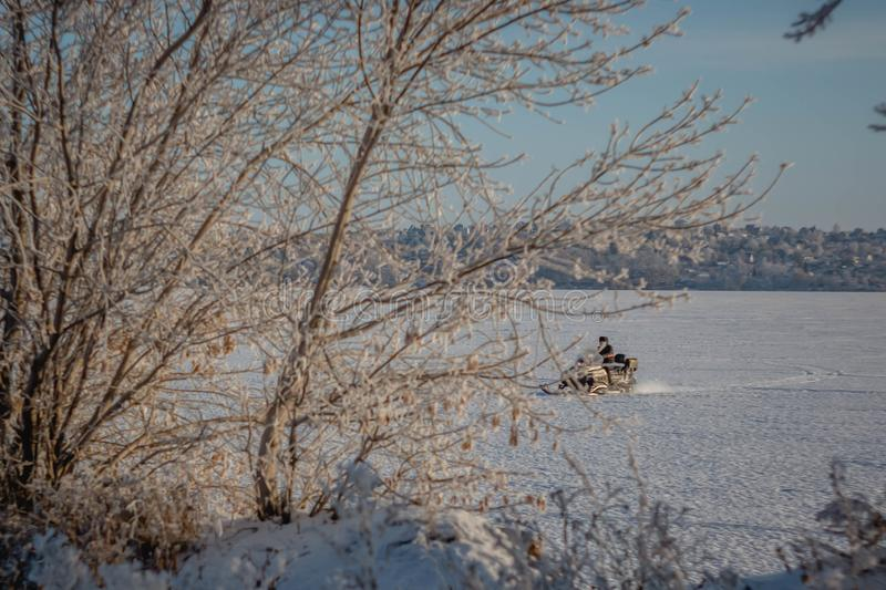 A man on a snowmobile rides a frozen river against a background of a blurry winter snowy rural landscape royalty free stock photo