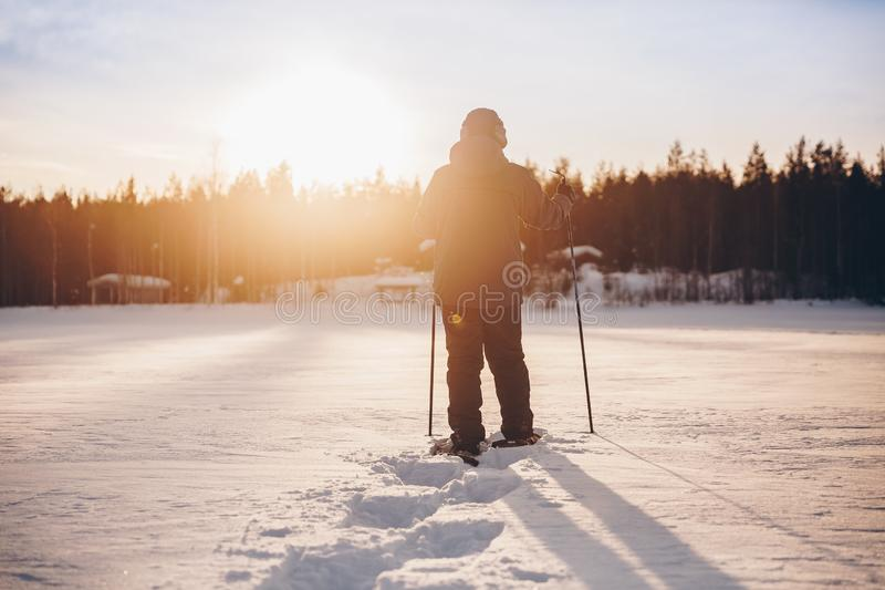 Man in snowshoes is walking with beautiful sunrise light. Outdoor winter activity stock photos