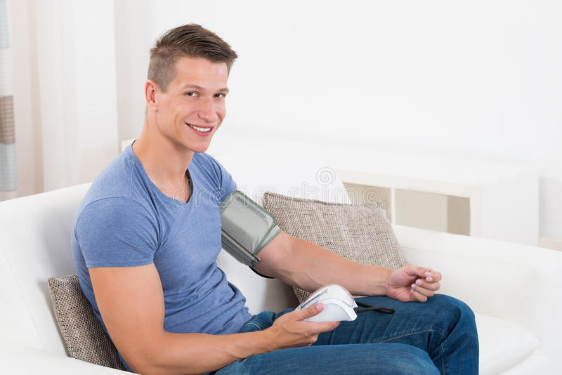 Man On Sofa Checking Blood Pressure. Young Happy Man Sitting On Sofa Checking Blood Pressure royalty free stock photography