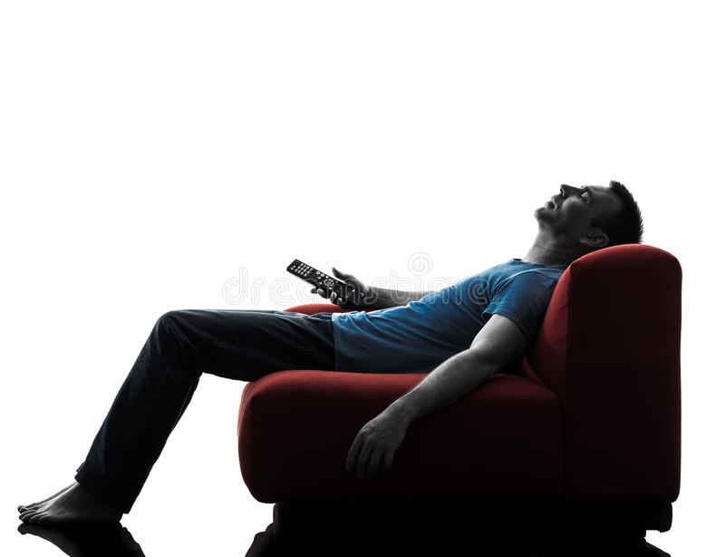Man sofa couch remote control sleeping watching tv. One caucasian man sofa couch remote control sleeping watching tv in silhouette isolated on white background royalty free stock photography