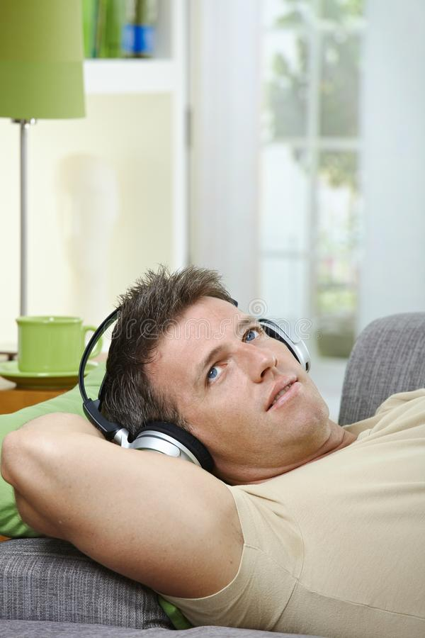 Man On Sofa Listening To Music Smiling Stock Photography