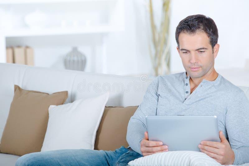 Man on sofa using tablet. Man stock photography