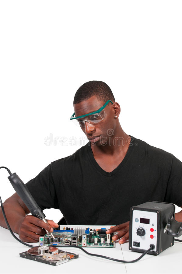 Man soldering. Man repairing a printed circuit board with a forced air soldering iron royalty free stock photography