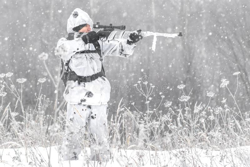 Man soldier in the winter on a hunt with a sniper rifle in white winter camouflage aiming standing in the snow stock images