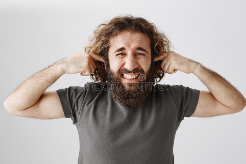 Man som äcklas från höga grannar Trött på vuxen man med lockigt hår och stängande öron för skägg med pekfingrar royaltyfri fotografi