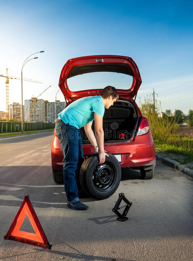 Man som ändrar det punkterade hjulet på den brutna bilen royaltyfria bilder