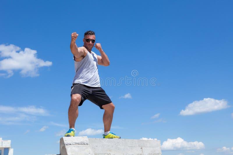 Man som är förlovad i karate mot himlen arkivfoto