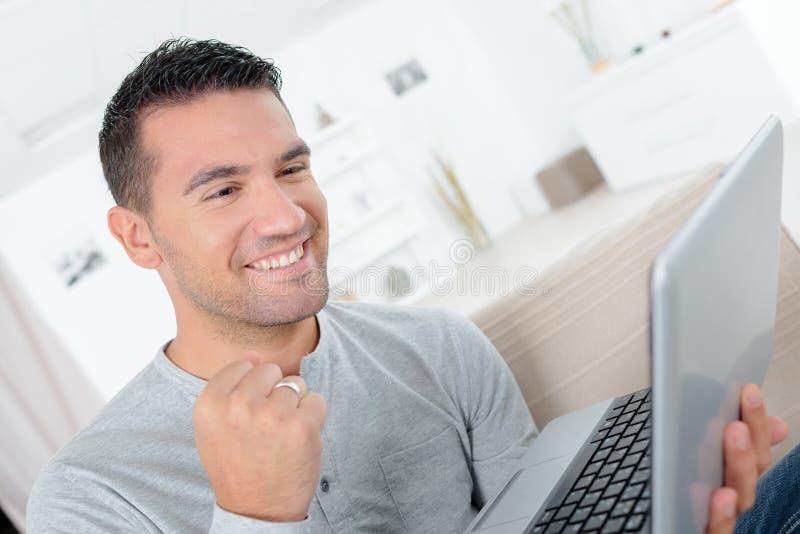 Man som är lycklig med online-resultat royaltyfria bilder
