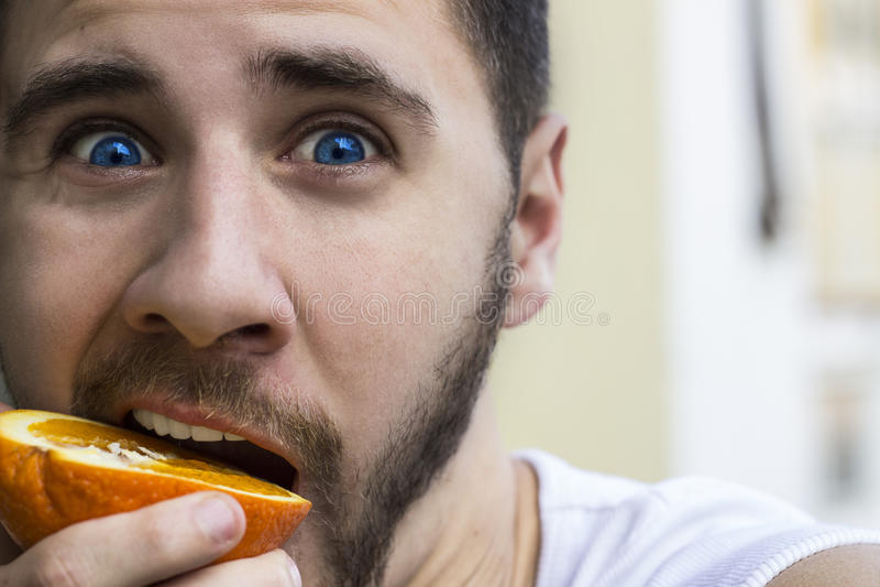 Man som äter apelsinen arkivbild