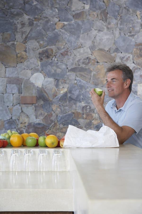 Man som äter Apple på diskbänken fotografering för bildbyråer