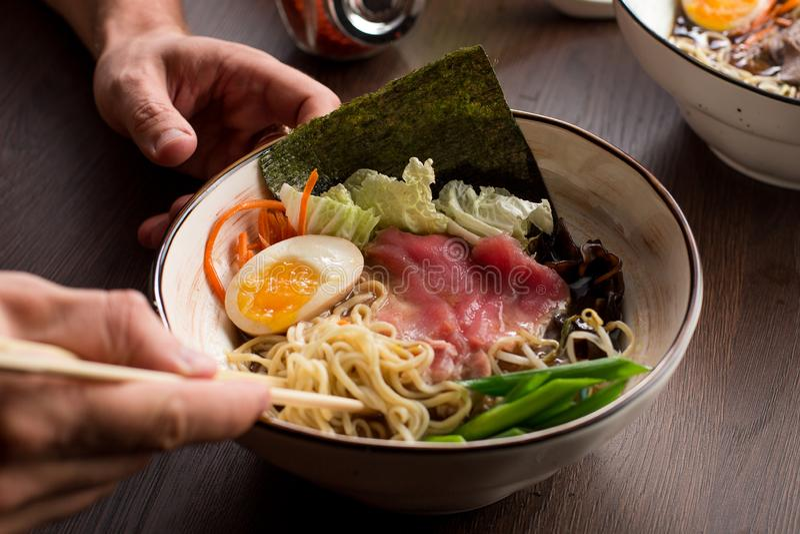 Man som äter asiatiska ramen med tonfisk och nudlar i en restaurang fotografering för bildbyråer