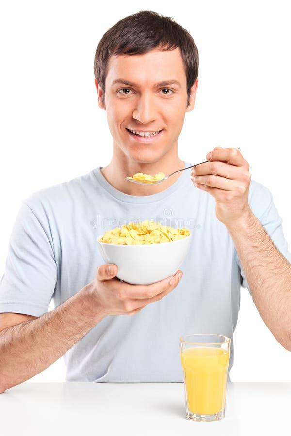 Man som äter cornflakes och dricker orange fruktsaft royaltyfria bilder