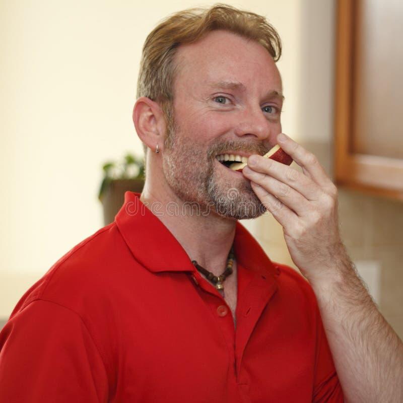 Man som äter den Apple skivan royaltyfria bilder