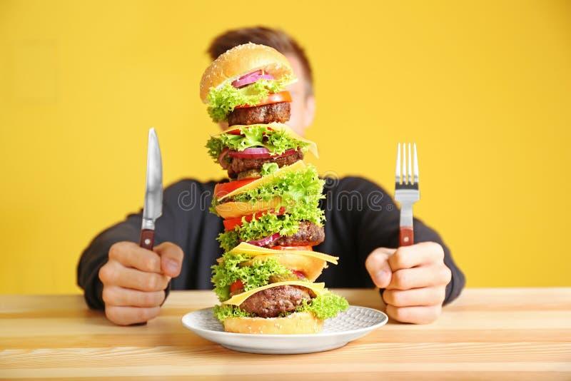 Man som äter den enorma hamburgaren på tabellen royaltyfri bild