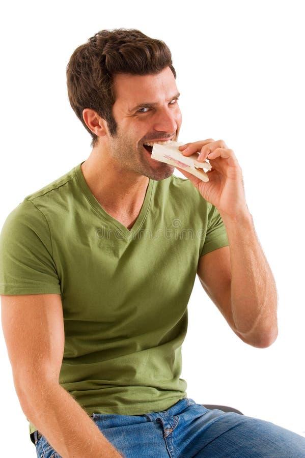 Man som äter en smörgås fotografering för bildbyråer