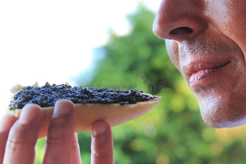 Man som äter en smörgås med den svarta kaviaren royaltyfri foto