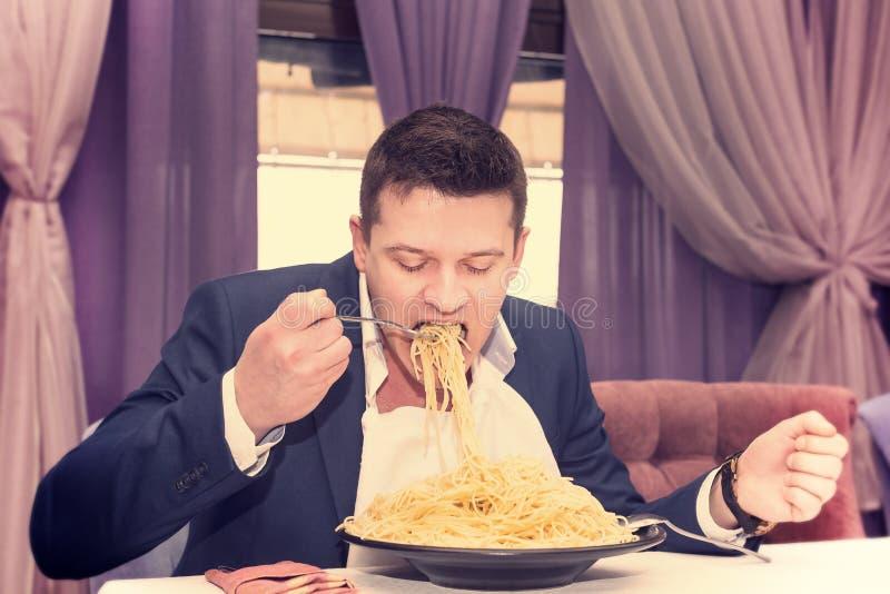 Man som äter en stor del av pasta arkivfoton