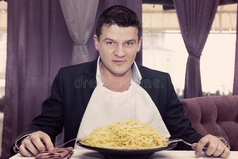 Man som äter en stor del av pasta fotografering för bildbyråer