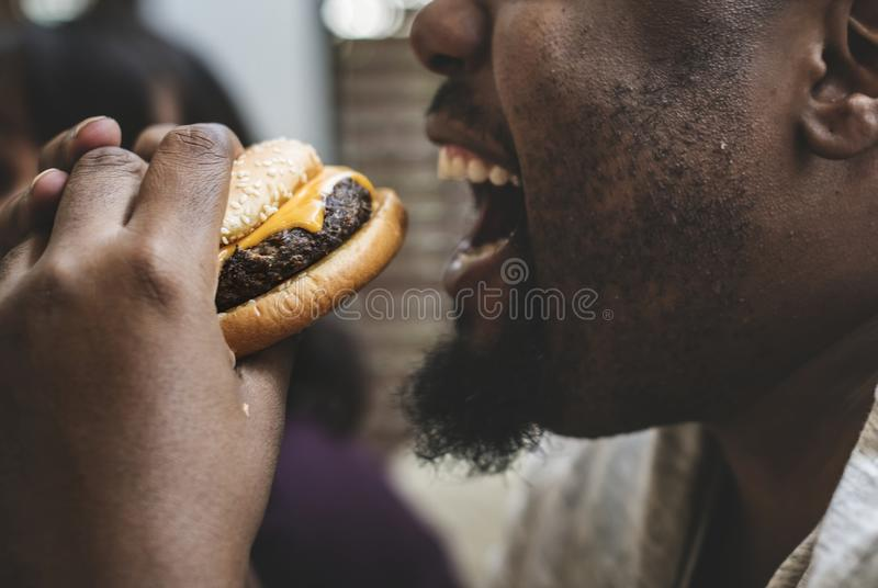 Man som äter en stor hamburgare arkivfoto