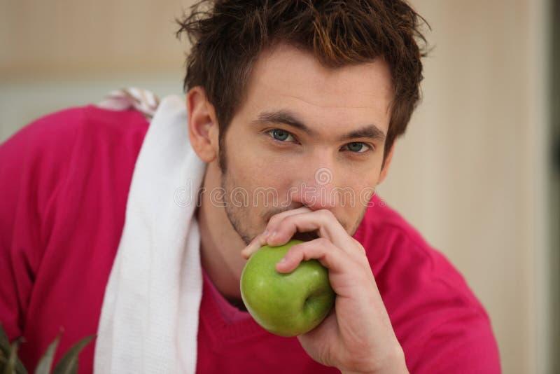 Man som äter ett äpple royaltyfria bilder