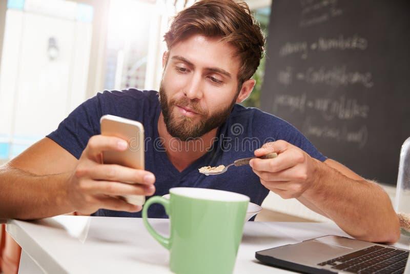 Man som äter frukoststund genom att använda mobiltelefonen och bärbara datorn arkivfoto