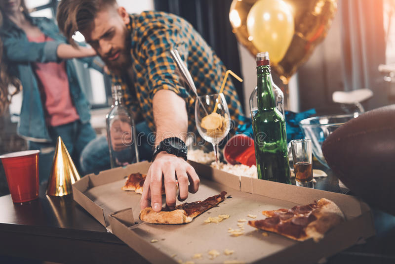 Man som äter gammal pizza i smutsigt rum royaltyfri bild
