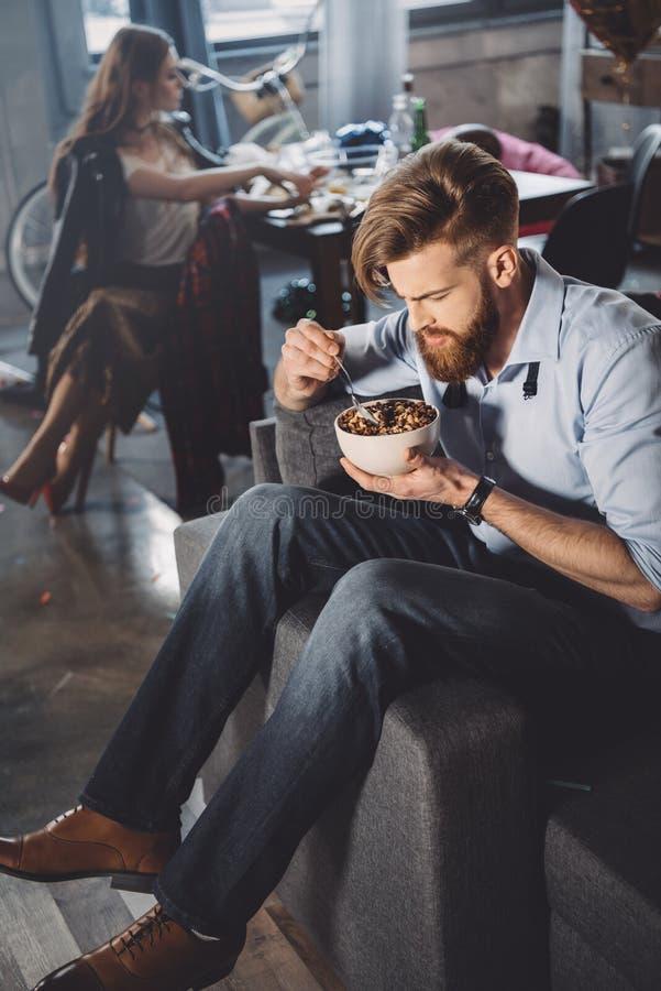 Man som äter havreflingor i smutsigt rum royaltyfri foto