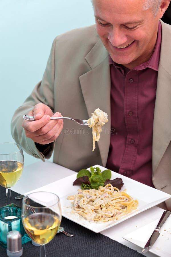 Man som äter pasta i en restaurang arkivbild