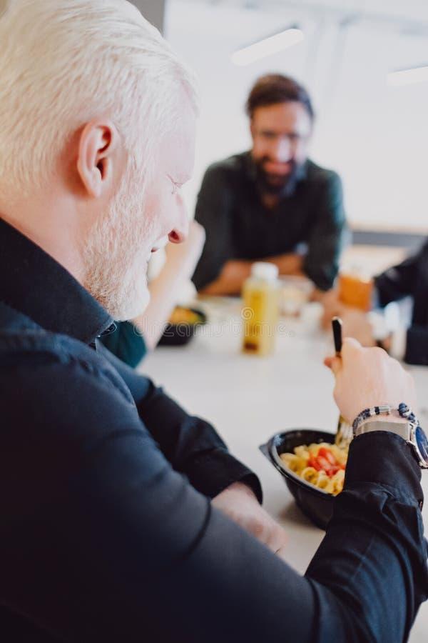 Man som äter pasta i kafeterian och le för kontor royaltyfria foton