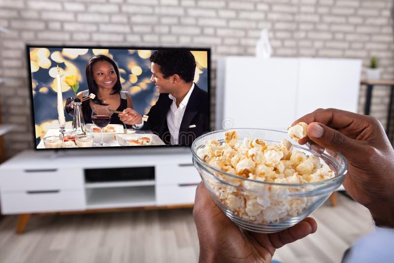 Man som ?ter popcorn, medan h?lla ?gonen p? television royaltyfri fotografi