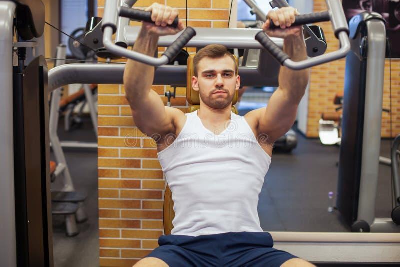 Man som övar på idrottshallen Konditionidrottsman nen som gör bröstkorgen, övar på den vertikala maskinen för bänkpress royaltyfri foto