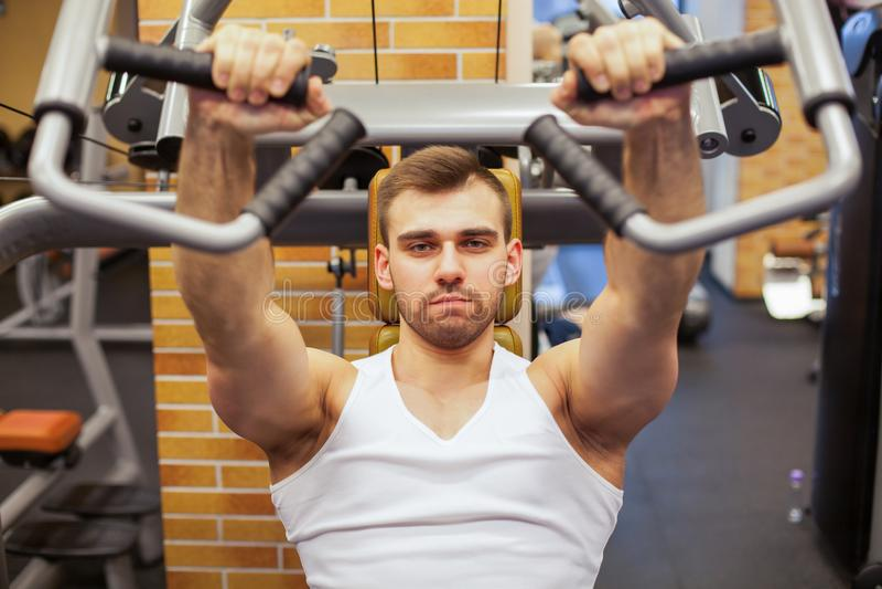 Man som övar på idrottshallen Konditionidrottsman nen som gör bröstkorgen, övar på den vertikala maskinen för bänkpress royaltyfria bilder