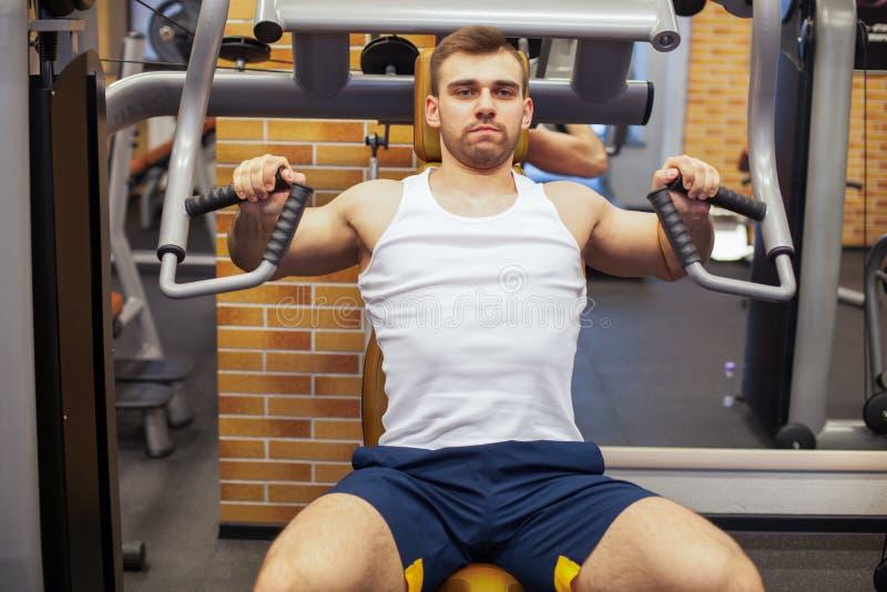 Man som övar på idrottshallen Konditionidrottsman nen som gör bröstkorgen, övar på den vertikala maskinen för bänkpress fotografering för bildbyråer