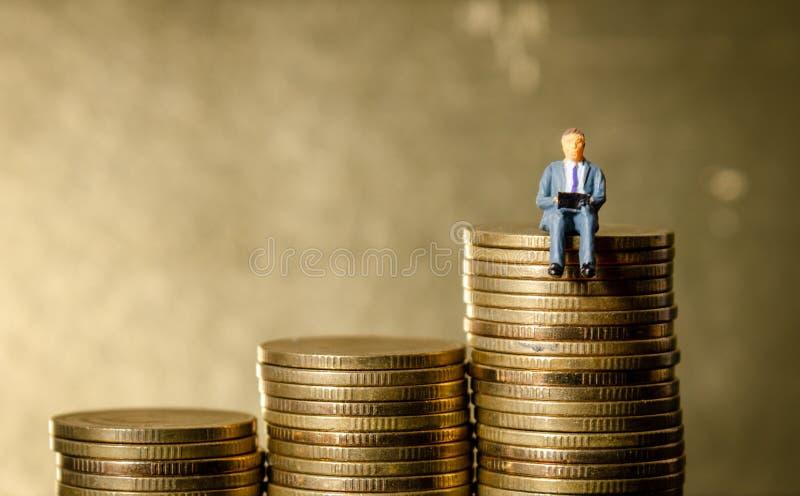 Man som överst sitter av högbunten av guld- mynt royaltyfri fotografi