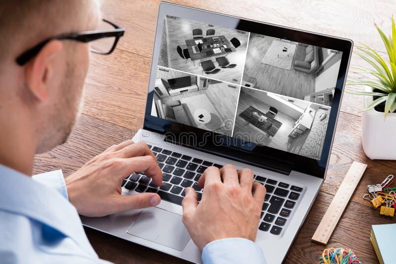 Man som övervakar videomaterialet på bärbara datorn arkivfoton