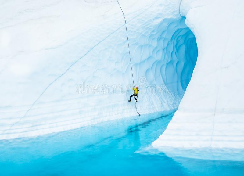 Man som absailing in i den översvämmade isgrottan på den Matanuska glaciären i Alaska fotografering för bildbyråer