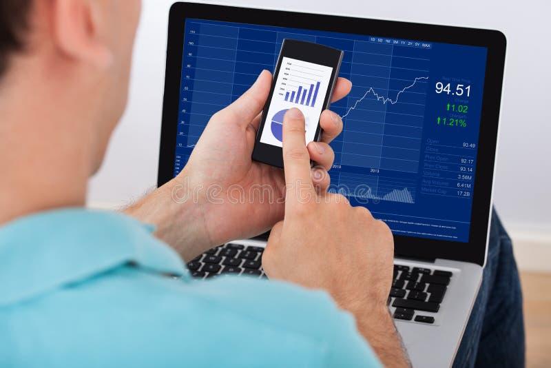 Man som analyserar aktiemarknaden genom att använda smartphonen och bärbara datorn fotografering för bildbyråer