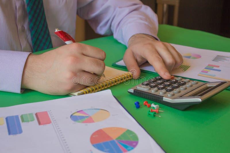 Man som analyserar finansiellt begrepp f?r statistik R?knemaskinerna, f?retags?garna, redovisningen och teknologin royaltyfri foto