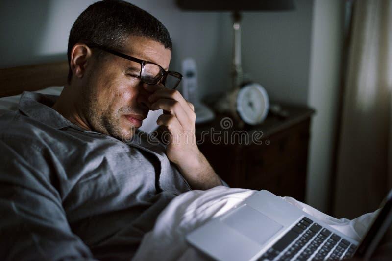 Man som använder bärbar dator på ett underlag arkivfoton