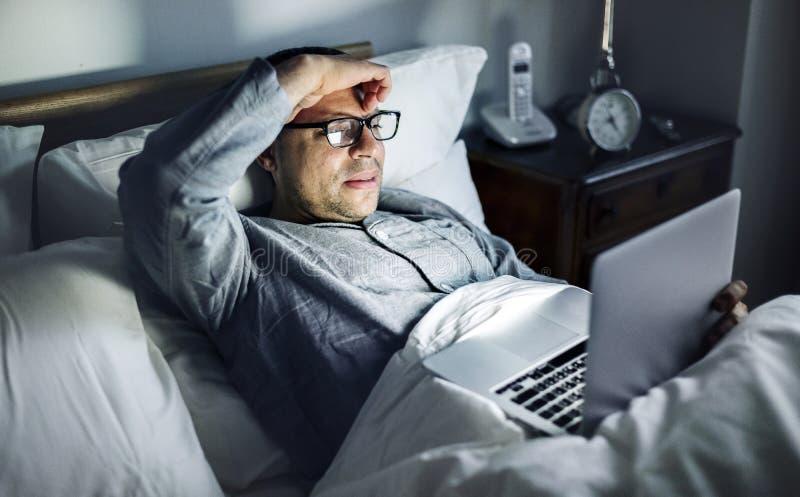 Man som använder bärbar dator på ett underlag royaltyfri foto