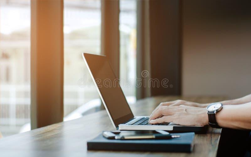 Man som använder bärbar datordatoren på coffee shop royaltyfria bilder