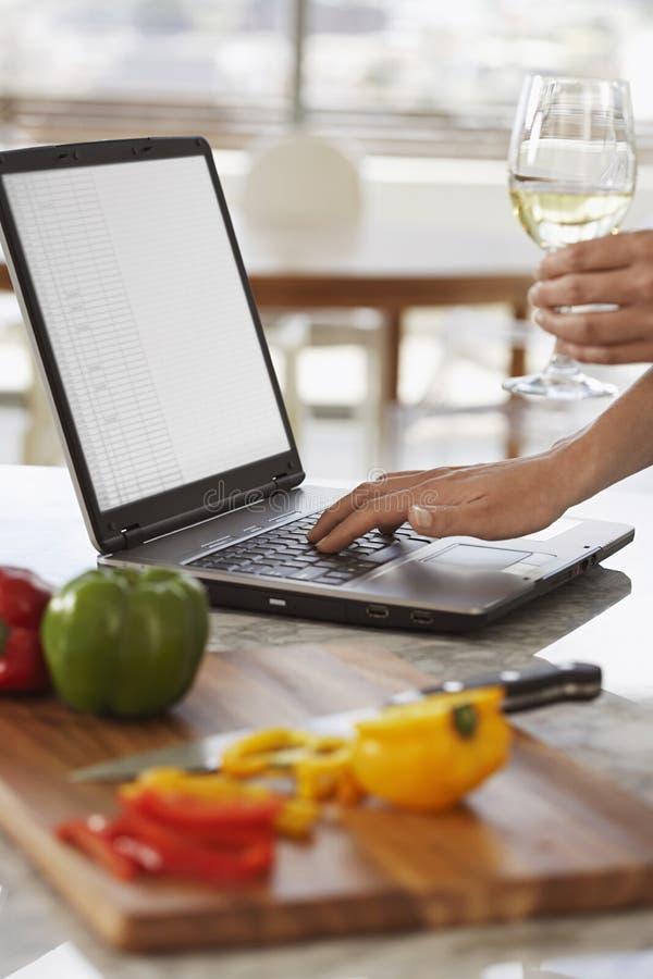 Man som använder bärbara datorn bredvid högg av Bellpepper i kök royaltyfri foto