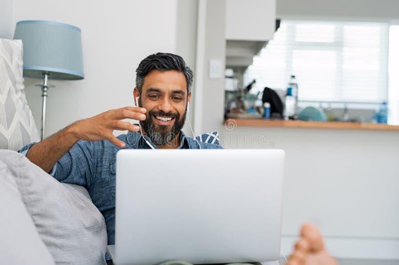 Man som använder bärbara datorn för den videopd appellen arkivfoto