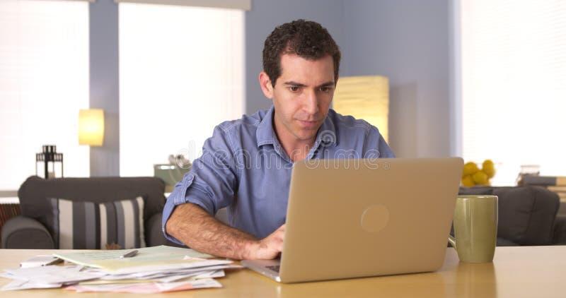 Man som använder bärbara datorn för online-bankrörelsen arkivbild