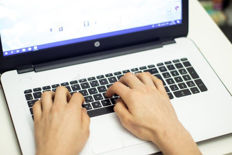 Man som använder bärbara datorn och att söka rengöringsduken som bläddrar information, arkivfoton