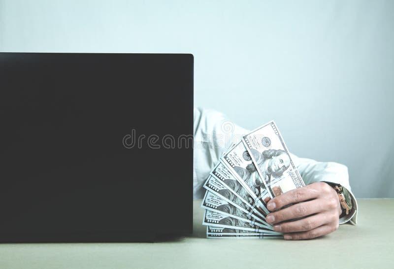 Man som använder bärbara datorn och visar pengar Begrepp av internetpengar arkivfoto