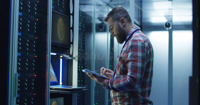 Man som använder bärbara datorn på att bryta lantgården i datorhall royaltyfria bilder
