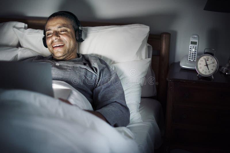 Man som använder bärbara datorn på en sängnattetid fotografering för bildbyråer