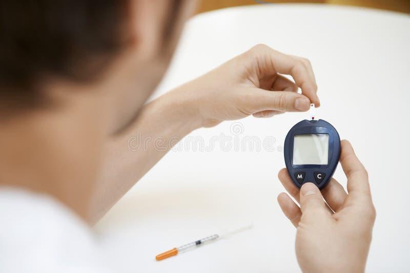 Man som använder blod Sugar Meter arkivbilder