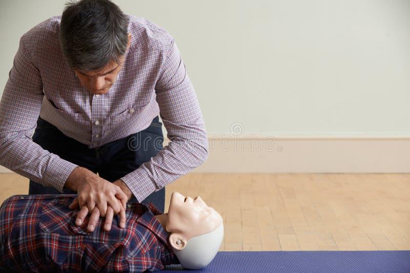 Man som använder CPR-teknik på attrapp i första hjälpengrupp arkivfoton